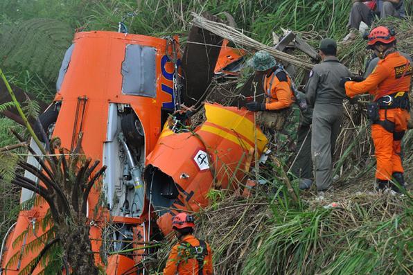 Membros de uma equipe indonésia de busca e resgate examinam os destroços de um helicóptero, depois que ele caiu em Temanggung, Java central no dia 02 de julho, deixando oito pessoas mortas.  Foto: AFP PHOTO / STR -