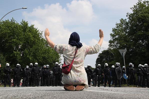 Uma manifestante detém suas mãos enquanto enfrenta policiais durante um protesto, em Hamburgo, no norte da Alemanha, onde líderes das principais economias do mundo se reúnem para uma cúpula do G20. Foto: AFP PHOTO / Ronny HARTMANN. -