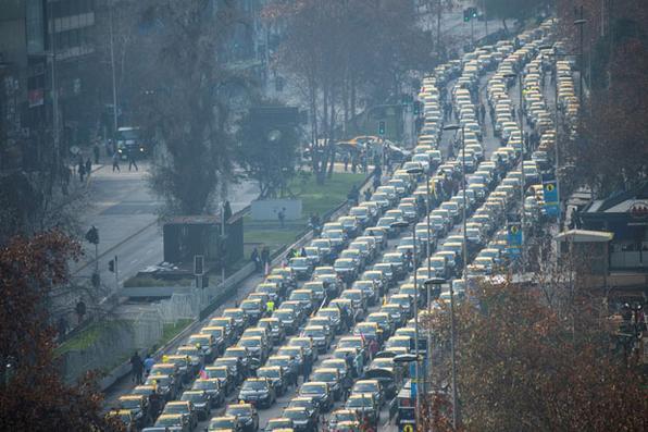 Os motoristas de táxi chilenos protestam, ao longo da Avenida Alameda, contra a Uber, do serviço de viagem a pedido dos EUA, em Santiago. Foto: AFP PHOTO / Martin BERNETTI.  -