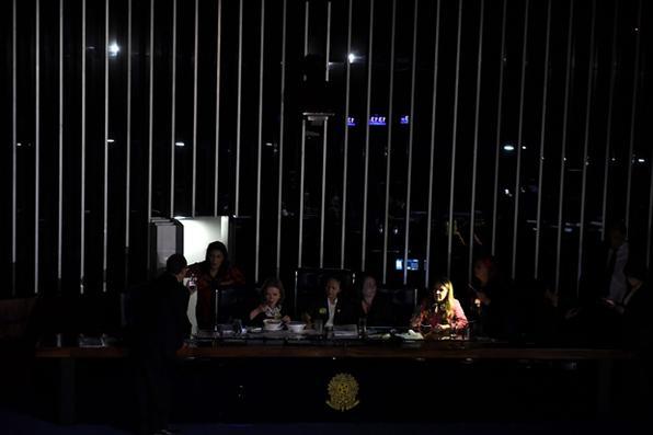 Senadores da oposição brasileira ocupam o discurso do senado contra a votação da reforma trabalhista , no Congresso Nacional de Brasília. As luzes do plenário foram apagadas por ordem do  presidente do Senado Eunicio Oliveira para neutralizar o protesto. Foto:  AFP PHOTO / EVARISTO SA -