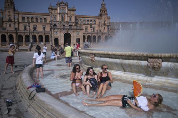 FOTOS DO DIA (Meninas refrescam em uma fonte da Plaza de Espana em Sevilha durante uma onda de calor. Foto:  AFP PHOTO / JORGE GUERRERO)