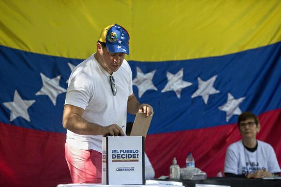 FOTOS DO DIA (Os venezuelanos que residem no Brasil participam de um plebiscito simbólico convocado pela oposição venezuelana no projeto do presidente Nicolas Maduro de uma futura assembléia constituinte, no Rio de Janeiro. Foto: AFP PHOTO / Mauro PIMENTEL.)
