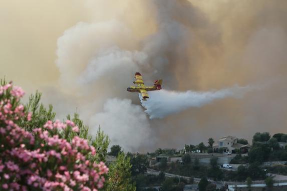 FOTOS DO DIA (Avião da Canadair joga água sobre um incêndio  em Castagniers, perto de Nice, na França. Foto: AFP PHOTO / Valery HACHE)