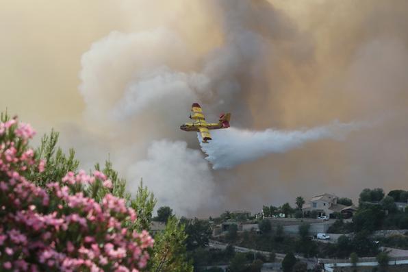 Avião da Canadair joga água sobre um incêndio  em Castagniers, perto de Nice, na França. Foto: AFP PHOTO / Valery HACHE -