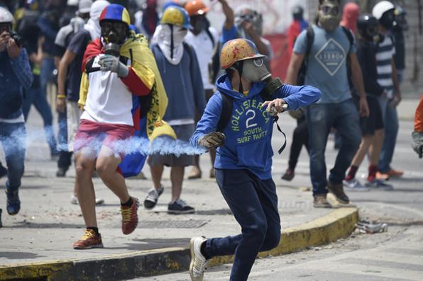 Ativistas mascarados da oposição entram em conflito com a polícia anti motim durante marcha em direção à Suprema Corte de Justiça (TSJ) em Caracas em uma ofensiva contra o presidente Maduro e seu apelo à Assembléia Constituinte em Caracas. Foto:  AFP PHOTO / JUAN BARRETO -
