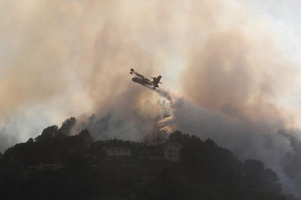 Uma aeronave canadense de combate a incêndio deixa cair água sobre um incêndio perto de Carros, no sudeste da França. Foto: AFP PHOTO / Valery HACHE. -