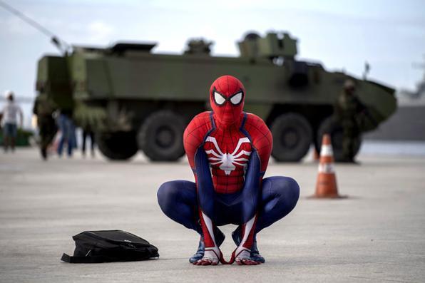 Homem fantasiado de homem aranha se coloca na frente de um navio de passageiros blindado da marinha brasileira, Foto: AFP PHOTO / Mauro PIMENTEL -