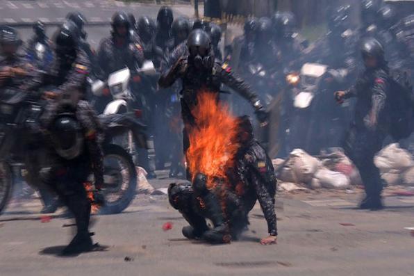 Policial pega fogo depois que  explosivo o atingiu durante protesto contra as eleições para uma Assembleia Constituinte em Caracas. Foto: AFP PHOTO / AFPTV / Leo RAMIREZ -
