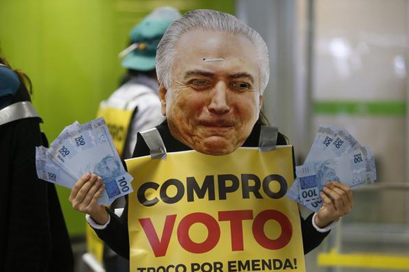 Ativistas da Avaaz usam máscaras do presidente Michel Temer e placas de ''Compro Voto'', ''distribuindo'' emendas orçamentárias e dinheiro a deputados que voltavam do recesso parlamentar no  Aeroporto de Brasília. Foto: DIDA SAMPAIO/ESTADÃO CONTEÚDO -