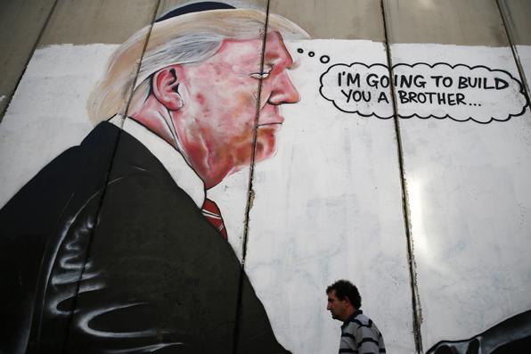 Um homem palestino passa por um graffiti que retrata o presidente dos EUA, Donald Trump, sobre o controverso muro de separação israelense na cidade de Belém, no oeste da Cisjordânia. AFP PHOTO / AHMAD GHARABLI - AFP PHOTO / AHMAD GHARABLI