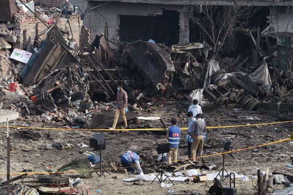 Segurança paquistanesa investiga local onde aconteceu explosão de bomba colocada dentro de um caminhão em Lahore na noite de ontem. Foto: AFP PHOTO / ARIF ALI -