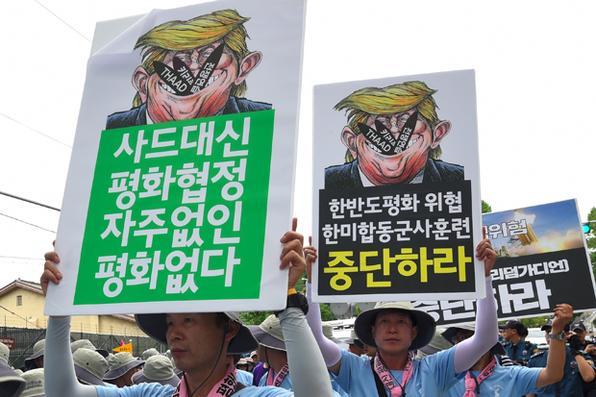 Sul-coreanos mantêm cartazes mostrando caricaturas do presidente norte-americano Donald Trump durante manifestação anti-EUA . Foto: AFP PHOTO / JUNG Yeon-Je -