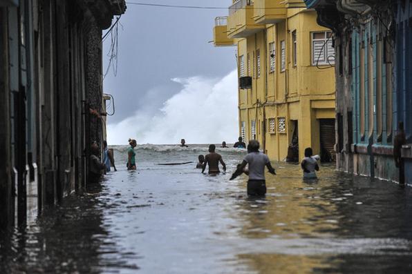 Cubanos atravessam rua inundada perto do Malecón em Havana. O furacão Irma derrubou linhas de energia, arrancou árvores e tirou  telhados das casas enquanto se dirigia para a Flórida. Foto:  AFP PHOTO / YAMIL LAGE -