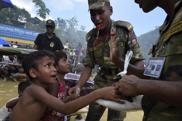 Soldados de Bangladesh distribuem arroz para jovens refugiados Rohingya no campo de refugiados de Balukhali, perto de Gumdhum. Foto: AFP PHOTO / DOMINIQUE FAGET -