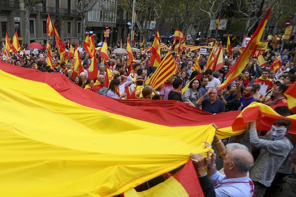 Manifestantes carregam uma gigantesca bandeira espanhola durante uma manifestação contra a independência na Catalunha, em Barcelona. Centenas de pessoas com bandeiras espanholas vermelhas e amarelas, se reuniram em Barcelona em favor da unidade espanhola hoje, um dia antes de um referendo de independência proibido na Catalunha. / AFP PHOTO / LLUIS GENE - / AFP PHOTO / LLUIS GENE