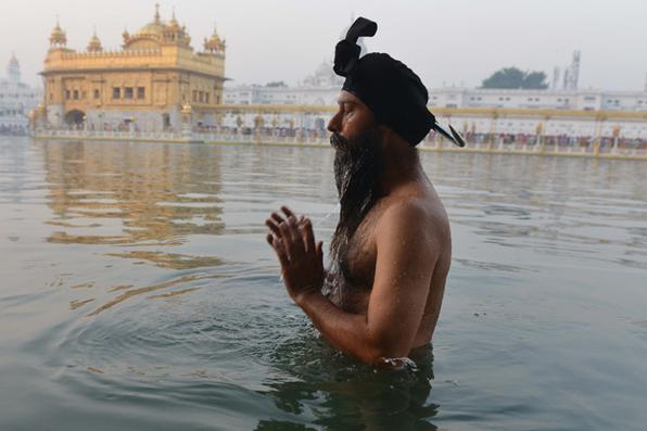 Um devoto do Sikh Indiano toma banho no tanque de água sagrada 'sarovar' durante o Festival de Diwali no Templo de Ouro iluminado em Amritsar. Diwali, o festival hindu das luzes, marca o triunfo do bem sobre o mal e comemora o retorno da deidade Hindu Rama ao local de nascimento, Ayodhya, depois da vitória contra o rei demoníaco Ravana. Foto: AFP PHOTO / Narrador NANU  -