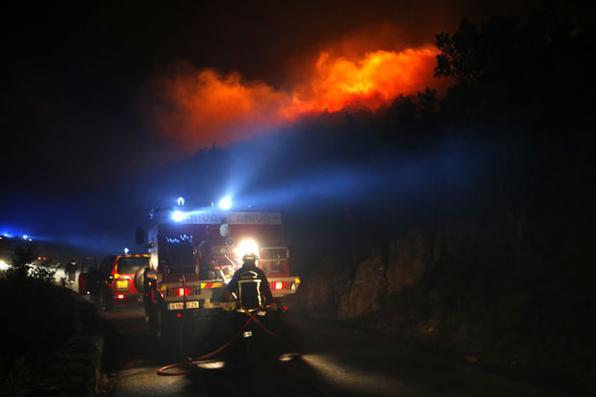 Os bombeiros lutam contra o fogo perto da vila de Palasca na Ilha do Mediterrâneo francês da Córsega. Um incêndio que começou no início do dia 22 de outubro e se expandiu por ventos de cerca de 100 quilômetros por hora, queimando cerca de 500 hectares na ilha, de acordo com as autoridades de combate a incêndios. / AFP PHOTO / PASCAL POCHARD-CASABIANCA -  AFP PHOTO / PASCAL POCHARD-CASABIANCA