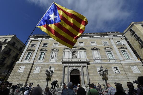 Uma pessoa acena uma bandeira catalã pró-independência em frente ao palácio ''Generalitat'' (sede do governo catalão) em Barcelona. A Espanha entra hoje no território inexplorado e potencialmente perigoso, enquanto Madrid se move para assumir o funcionamento da Catalunha em resposta ao parlamento da região rebelde, declarando unilateralmente a independência. AFP PHOTO / LLUIS GENE -  AFP PHOTO / LLUIS GENE