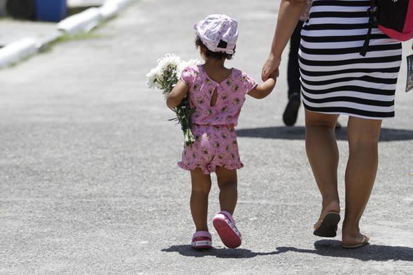 Criança ao lado de sua mãe, no cemitério de Santo Amaro, na cidade do Recife, no feriado de Finados. Foto: Ricardo Fernandes/ Diario de Pernambuco.  -