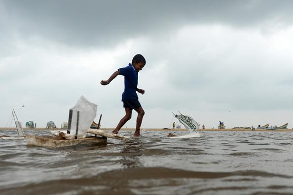 Criança indiana brinca na água da inundação em Marina Beach na costa da Baía de Bengala depois de fortes chuvas em Chennai. Foto: AFP PHOTO / ARUN SANKAR -