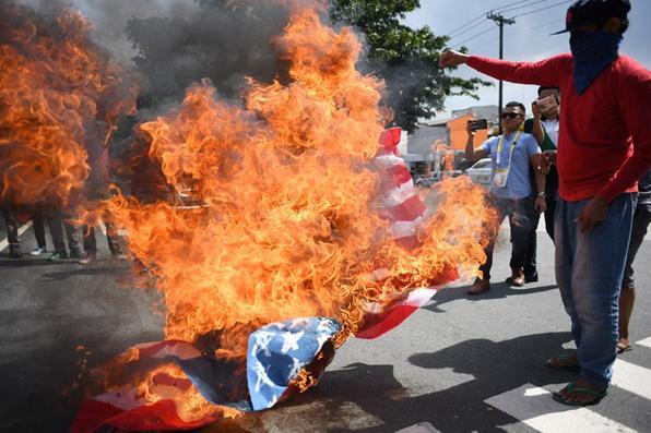Os manifestantes queimam uma bandeira dos EUA durante um protesto fora do Centro de Convenções contra a próxima visita do presidente dos EUA, Donald Trump, antes do início da Sessão da 31ª Associação das Nações do Sudeste Asiático (ASEAN) em Manila. AFP PHOTO / Noel CELIS - AFP PHOTO / Noel CELIS