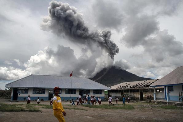 Crianças jogam em uma escola primária, quando o vulcão Monte Sinabung cume fumaça em Karo. Sinabung rugiu de volta à vida em 2010 pela primeira vez em 400 anos, depois de outro período de inatividade, ele entrou em erupção mais uma vez em 2013 e permaneceu altamente ativo desde então. Foto: AFP PHOTO / Ivan DAMANIK. -