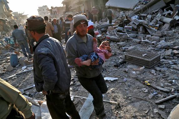 """FOTOS DO DIA (Um homem sírio carrega uma criança após um acidente aéreo na cidade de Atareb, na cidade de Aleppo, na cidade de Alema. Pelo menos 21 civis foram mortos em ataques aéreos na província de Aleppo, na Síria, apesar de uma """"zona de escalada"""" no local, afirmou o Observatório Sírio dos direitos humanos, com sede em Grã-Bretanha.  / AFP PHOTO / Zein Al RIFAI)"""