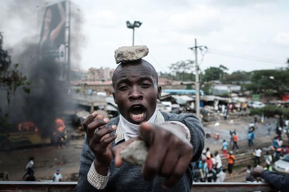 Os partidários do partido de oposição do Quênia National Super Alliance (NASA) reagem durante uma manifestação após a chegada do líder da oposição Raila Odinga ao aeroporto Jomo Kenyatta International em Nairobi. Três homens foram mortos a tiros quando o líder da oposição, Raila Odinga, retornou ao Quénia, com a polícia disparando gás lacrimogêneo em seu convoy e torcedores, segundo um repórter da AFP. / AFP PHOTO / YASUYOSHI CHIBA -  AFP PHOTO / YASUYOSHI CHIBA