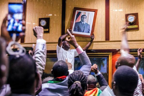 As pessoas removem o retrato do ex-presidente zimbabuense, Robert Mugabe, após sua demissão, em Harare. Foto: AFP PHOTO / Jekesai NJIKIZANA. -
