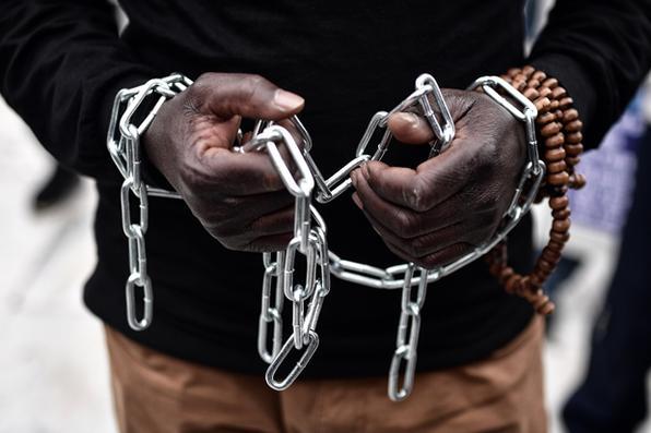 Imigrante africano com as mãos acorrentadas, participa de marcha no centro de Atenas, protestando contra a escravidão dos imigrantes na Líbia e contra os acordos entre a União Européia (UE ) e Turquia e entre a UE e a Líbia. Foto: AFP PHOTO / LOUISA GOULIAMAKI -