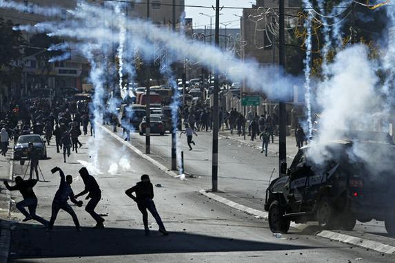 FOTOS DO DIA (Manifestantes palestinos jogam pedras sobre as forças israelenses durante confrontos perto de um ponto de controle israelense na cidade de Belém, em Cisjordânia, na sequência da decisão do presidente dos EUA de reconhecer a cidade de Jerusalém como a capital de Israel. Foto:AFP PHOTO / Musa AL SHAER.)