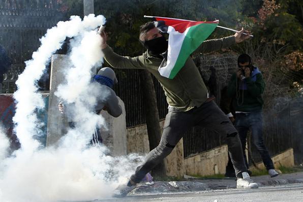 Um manifestante palestino lança uma armadilha de gás lacrimoso para as forças israelenses durante os confrontos na entrada principal da cidade de Belém, no Cisjordânia, após uma manifestação contra a decisão do presidente dos EUA, Donald Trump, de reconhecer Jerusalém como a capital de Israel. Foto: AFP PHOTO / Musa AL SHAER. -