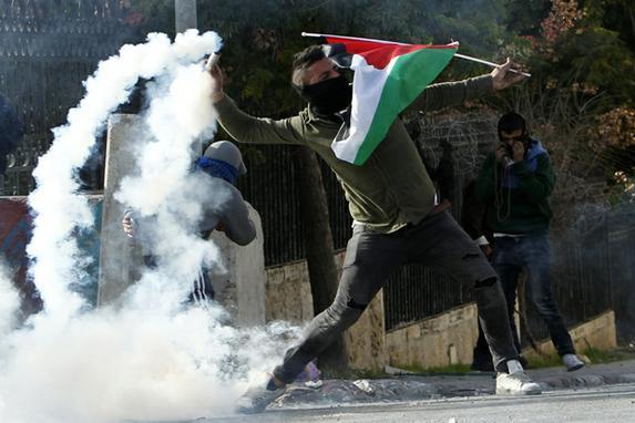 FOTOS DO DIA (Um manifestante palestino lança uma armadilha de gás lacrimoso para as forças israelenses durante os confrontos na entrada principal da cidade de Belém, no Cisjordânia, após uma manifestação contra a decisão do presidente dos EUA, Donald Trump, de reconhecer Jerusalém como a capital de Israel. Foto: AFP PHOTO / Musa AL SHAER.)