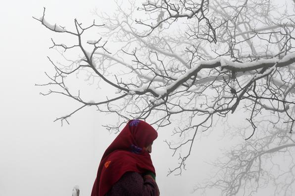 Residente da Caxemira caminha após  queda de neve  nos arredores de Srinagar. Foto:  AFP PHOTO / Tauseef MUSTAFA -