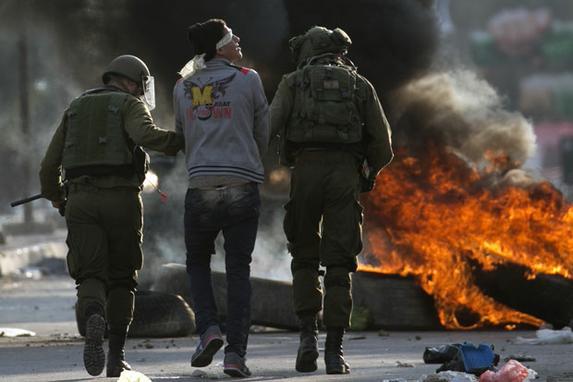 FOTOS DO DIA (As forças de segurança israelenses prenderam um manifestante palestino perto do ponto de verificação de Huwara, ao sul de Nablus, na Cisjordânia ocupada pelos israelenses, à medida que os protestos continuam na região em meio à ira sobre o reconhecimento do presidente dos EUA, Donald Trump, de Jerusalém como sua capital. Foto: AFP PHOTO / JAAFAR ASHTIYEH.)