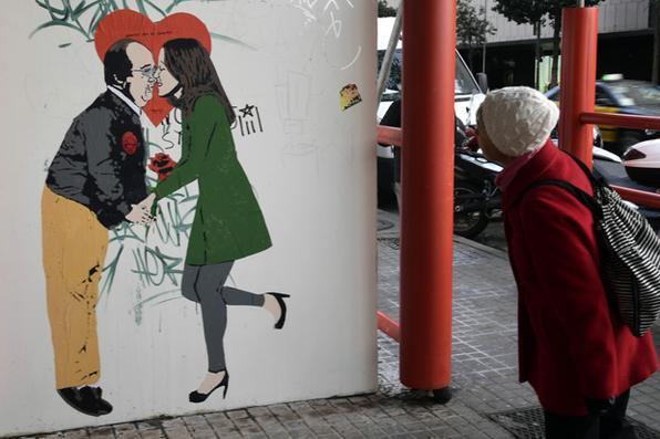 Uma mulher olha para um cartaz de arte de rua do artista urbano italiano Salvatore Benintende aka ''TVBOY'' que representa o Partido Socialista da Catalã - candidato do PSC Miquel Iceta beijando o candidato do centro-direita do candidato Ciudadanos (Cidadãos) para a próxima eleição regional catalã Ines Arrimadas em Barcelona na véspera do dia das eleições.  Foto:  AFP PHOTO / JAVIER SORIANO. -