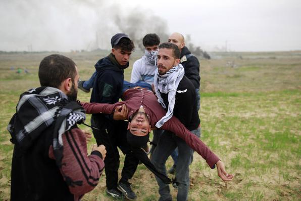 Manifestantes palestinos carregam um camarada ferido durante confrontos com soldados israelenses perto da cerca da fronteira a leste da cidade de Gaza. Foto: Mohammed Abed/ AFP Photo -