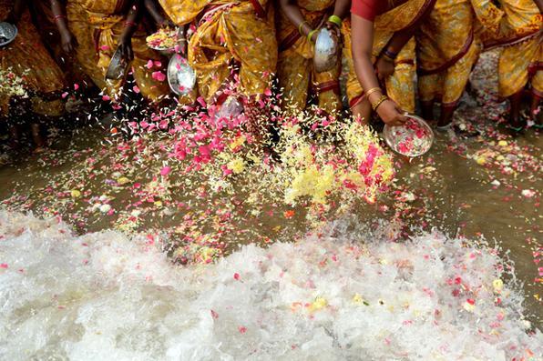 Mulheres indianas lançam flores no mar como uma oferta durante uma cerimônia para as vítimas do tsunami de 2004 na praia de Pattinapakkam, em Chennai. Foto: AFP PHOTO / ARUN SANKAR.  -