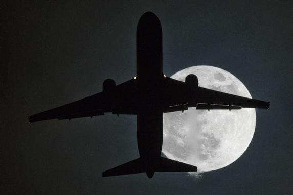 """FOTOS DO DIA (Um avião voa na frente de uma """"super lua"""" em sua aproximação ao aeroporto de Londres Heathrow. Foto: AFP PHOTO / Justin TALLIS.)"""