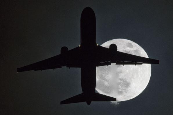 Um avião voa na frente de uma ''super lua'' em sua aproximação ao aeroporto de Londres Heathrow. Foto: AFP PHOTO / Justin TALLIS. -