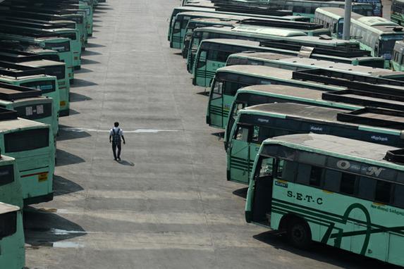 FOTOS DO DIA (Um homem indiano atravessa os ônibus estacionados em um depósito durante uma greve de transporte em Chennai. Foto: AFP PHOTO / ARUN SANKAR.)