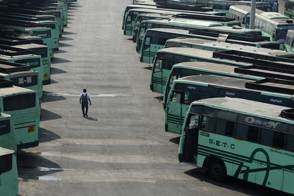 Um homem indiano atravessa os ônibus estacionados em um depósito durante uma greve de transporte em Chennai. Foto: AFP PHOTO / ARUN SANKAR. -