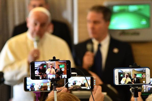 Os jornalistas usam seus telefones para gravar um vídeo enquanto o Papa Francisco faz uma conferência de imprensa a bordo do avião papal em Roma, antes de partir para o Chile. AFP PHOTO / Vincenzo PINTO - AFP PHOTO / Vincenzo PINTO