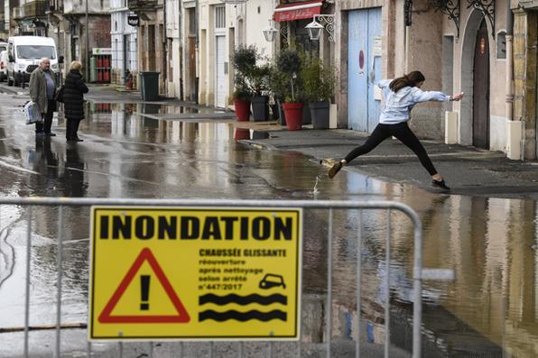Mulher salta sobre uma poça ao longo dos rios inundados do rio Saone em Tournus, no leste da França. Foto: AFP PHOTO / PHILIPPE DESMAZES. -