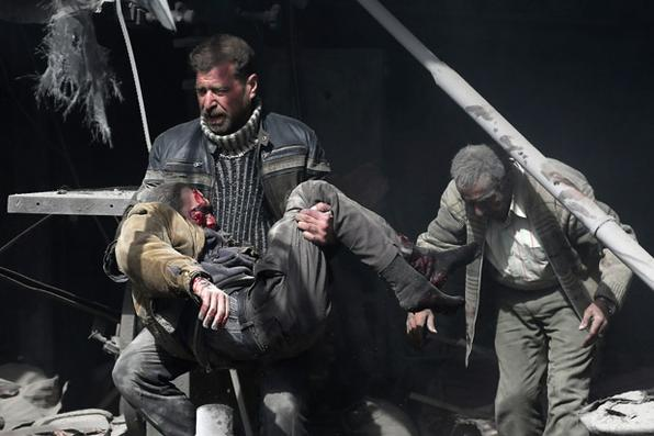 Um homem sírio carrega uma vítima ferida em meio a escombros de edifícios após o bombardeio do governo na cidade rebelde de Hamouria, na região sitiada de Ghouta Oriental, nos arredores da capital Damasco. O pesado bombardeio sírio matou 44 civis no Ghouta oriental , já que as forças do regime pareciam se preparar para um ataque iminente no solo. / AFP PHOTO / ABDULMONAM EASSA -  AFP PHOTO / ABDULMONAM EASSA