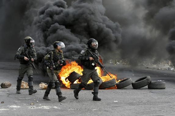 FOTOS DO DIA (Guardas da fronteira israelenses avançam por uma rua durante confrontos com manifestantes palestinos na cidade de Ramallah, no Cisjordânia, contra uma decisão do presidente dos EUA, Donald Trump, de reconhecer Jerusalém como a capital de Israel. / AFP PHOTO / ABBAS MOMANI )