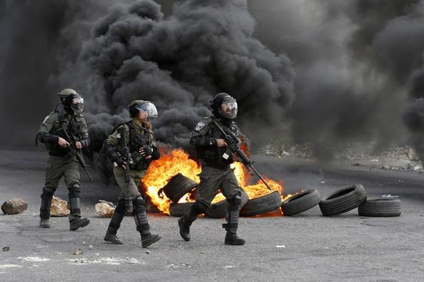 Guardas da fronteira israelenses avançam por uma rua durante confrontos com manifestantes palestinos na cidade de Ramallah, no Cisjordânia, contra uma decisão do presidente dos EUA, Donald Trump, de reconhecer Jerusalém como a capital de Israel. / AFP PHOTO / ABBAS MOMANI -  AFP PHOTO / ABBAS MOMANI