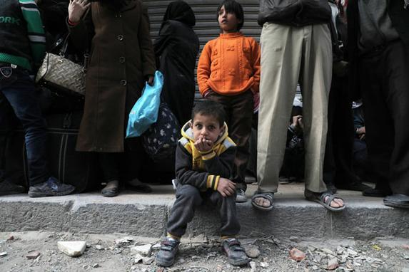 FOTOS DO DIA (Os sírios esperam na rua quando um comboio humanitário que transporta comida chega na cidade rebelde de Douma, em Ghouta Oriental, nos subúrbios a leste da capital Damasco. Foto: AFP PHOTO / HAMZA AL-AJWEH.)