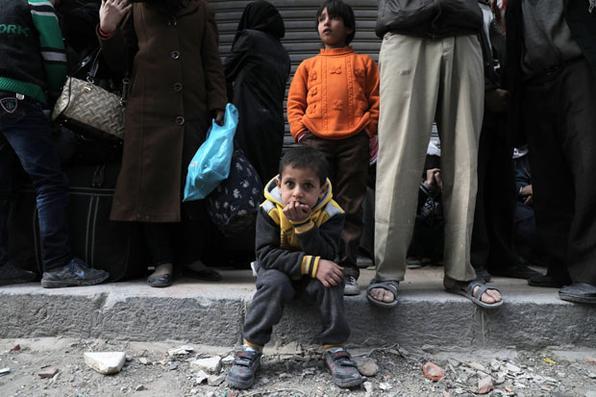 Os sírios esperam na rua quando um comboio humanitário que transporta comida chega na cidade rebelde de Douma, em Ghouta Oriental, nos subúrbios a leste da capital Damasco. Foto: AFP PHOTO / HAMZA AL-AJWEH. -