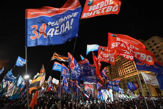 FOTOS DO DIA (As pessoas participam de uma manifestação e de um concerto comemorando o quarto aniversário da anexação da Criméia na Praça Manezhnaya em Moscoude. / AFP PHOTO / Kirill KUDRYAVTSEV)
